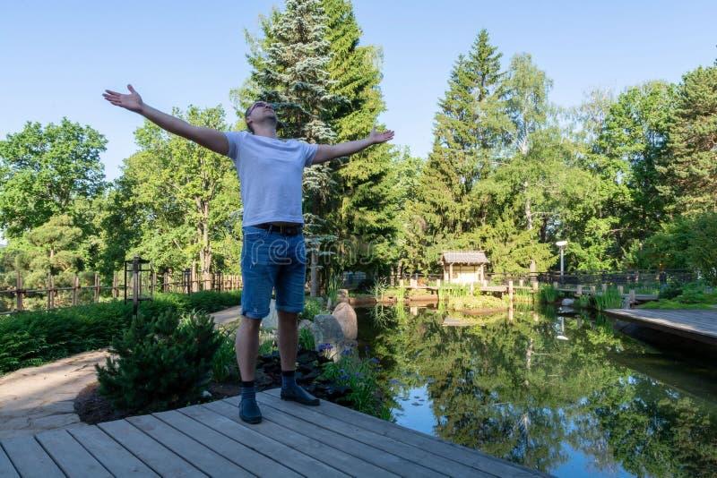 Un jeune homme rencontre l'aube, se tenant devant un étang avec des bras au loin distants et tournant son visage au ciel photo libre de droits