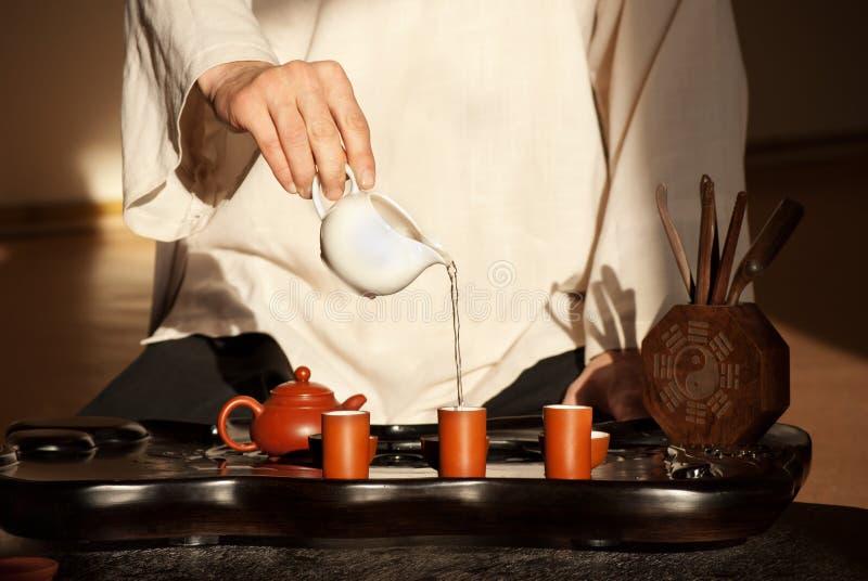 Un jeune homme retient une cérémonie de thé chinoise images stock