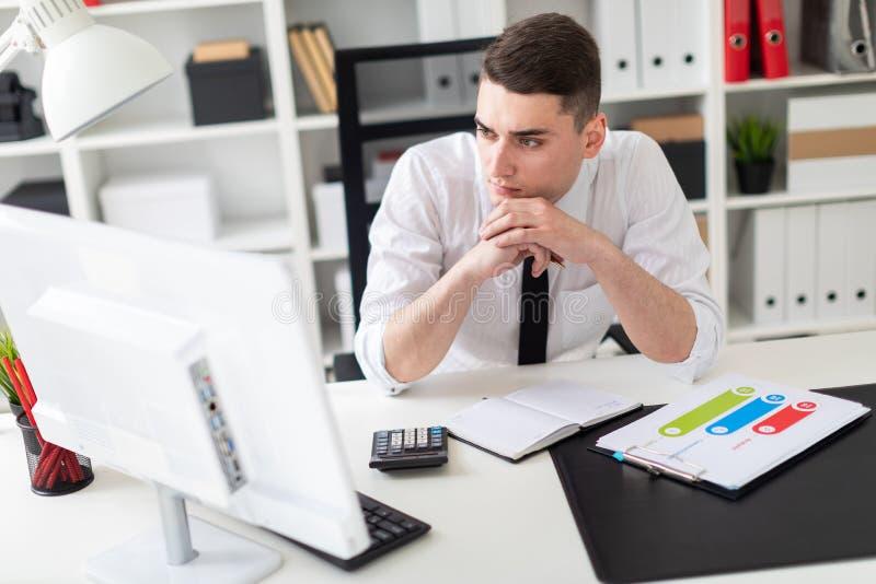 Un jeune homme s'asseyant à un bureau d'ordinateur dans le bureau et travaillant avec des documents image stock