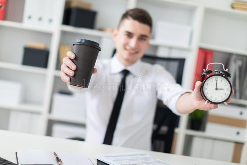 Un jeune homme s'asseyant à une table dans le bureau et tenant un verre de café et d'un réveil Photo avec la profondeur du champ photographie stock