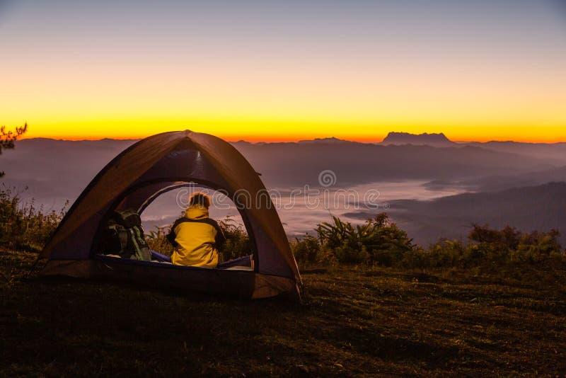 Un jeune homme s'asseyant dans une tente tout en observant le paysage de montagne en hiver photos stock