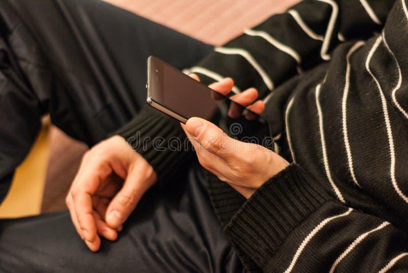 Un jeune homme, s'asseyant sur le divan pour se reposer avec un smartphone dans l'ha photographie stock libre de droits