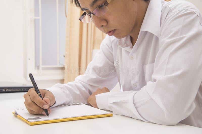 Un jeune homme s'assied à une table et écrit dans un carnet photos libres de droits