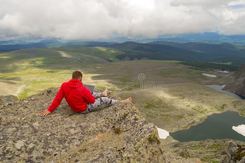 Un jeune homme s'assied nu-pieds avec un ordinateur portable dans son travail de mains comme f photographie stock libre de droits