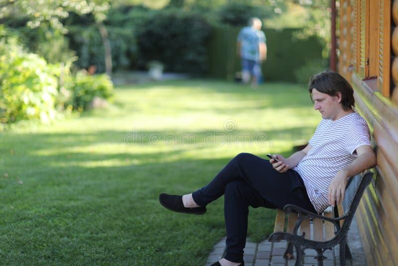 Un jeune homme s'assied sur un banc de jardin photos libres de droits
