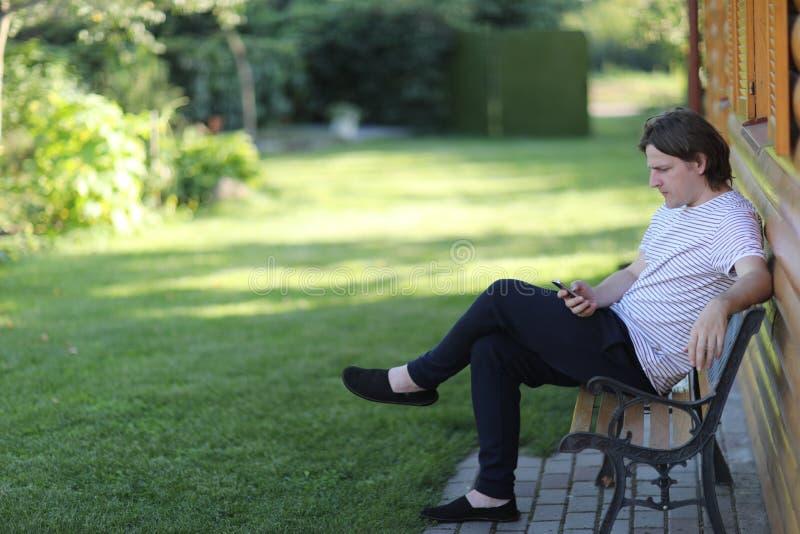 Un jeune homme s'assied sur un banc de jardin image stock