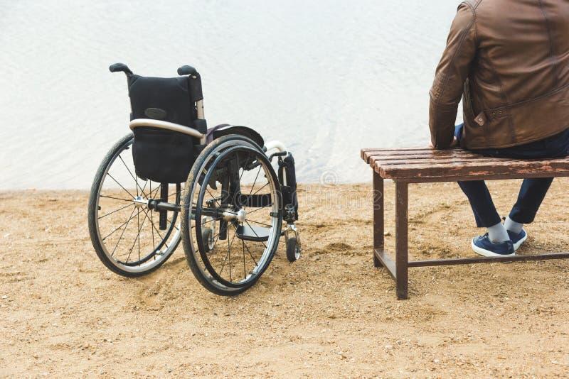 Un jeune homme s'assied sur un banc par le lac, à côté de son fauteuil roulant image libre de droits