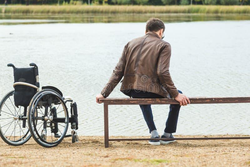Un jeune homme s'assied sur un banc par le lac, ? c?t? de son fauteuil roulant photos stock