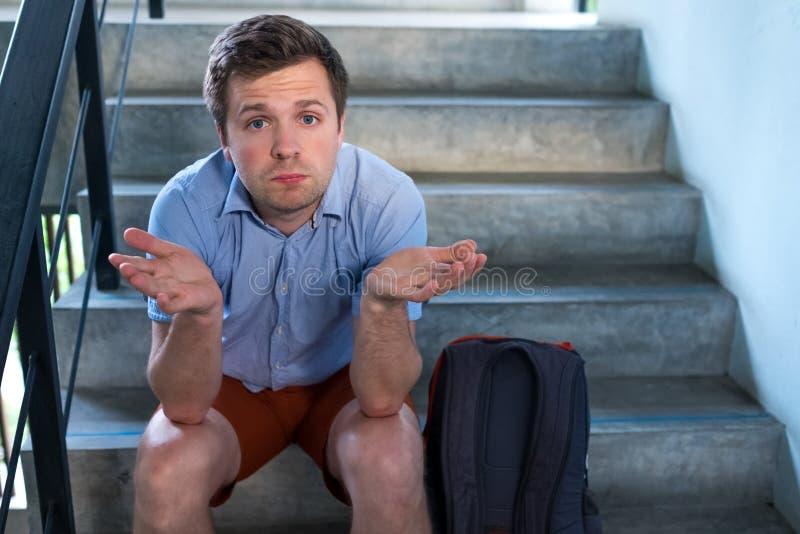 Un jeune homme s'assied sur les escaliers et triste Il a perdu les clés à l'appartement, image libre de droits