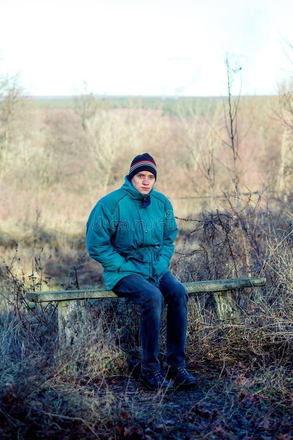 Un jeune homme s'assied sur un vieux banc dans la campagne en automne photos stock