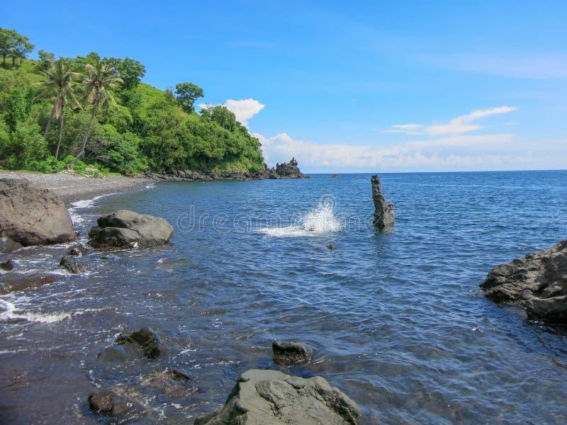 Un jeune homme saute d'un rocher dans l'eau Les falaises des formes abstraites dépassent au-dessus de la surface Cristal - eau de images libres de droits