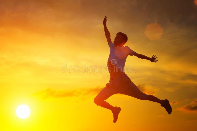 Un jeune homme saute jusqu'au dessus sur le fond du coucher du soleil images stock