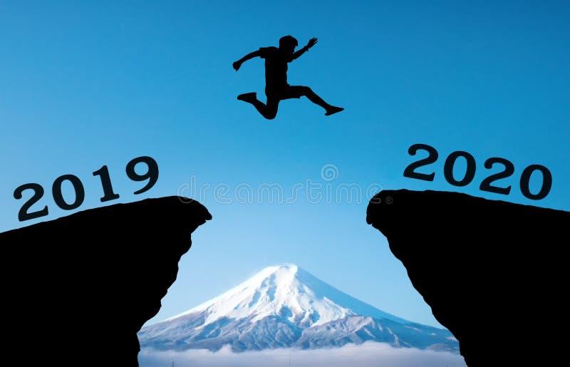Un jeune homme sautent entre 2019 et 2020 ans au-dessus du soleil et sur l'espace du ciel coloré de soirée de silhouette de colli image libre de droits