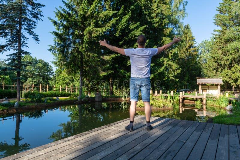 Un jeune homme se tient à l'aube devant un étang avec ses bras augmentés au ciel photographie stock