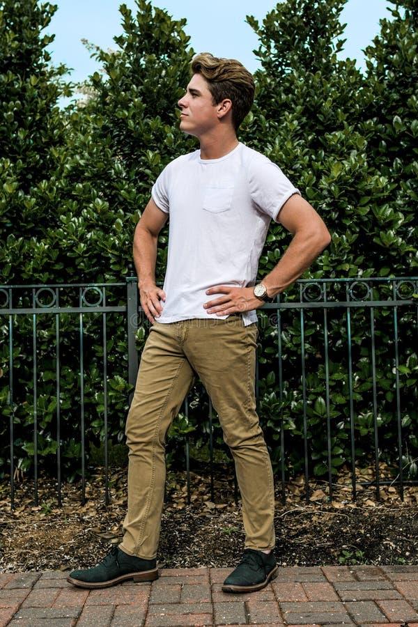 Un jeune homme se tient posant pour l'appareil-photo image libre de droits