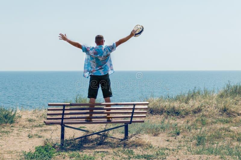 Un jeune homme se tient sur un banc avec ses bras augment?s et appr?cie la vue de la mer image libre de droits