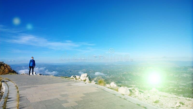 Un jeune homme se tient sur un chemin au mausolée sur Lovcen dans Monténégro Vues panoramiques des montagnes et des champs photos libres de droits