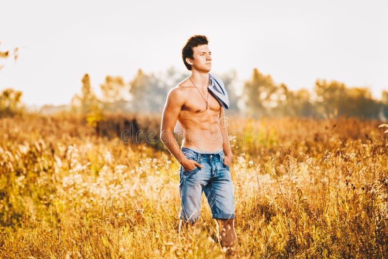 Un jeune homme sexy beau avec un torse musculaire fort dans une chemise déboutonnée se tient sur un pré en nature en dehors de vi photo stock