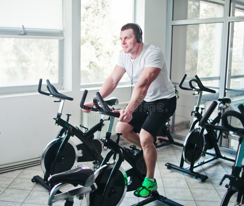 Un jeune homme sportif en T-shirt blanc et short fait de l'exercice à vélo en classe de rotation images libres de droits