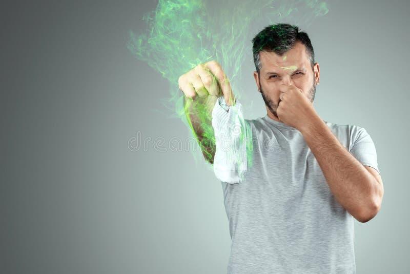 Un jeune homme tient ses chaussettes odorantes et se couvre le nez de la main Odeur de mauvais goût Pieds puants, champignon sur  image stock