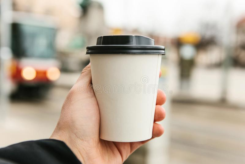Un jeune homme tient un verre jetable avec du café ou une boisson chaude différente pendant la saison froide image libre de droits