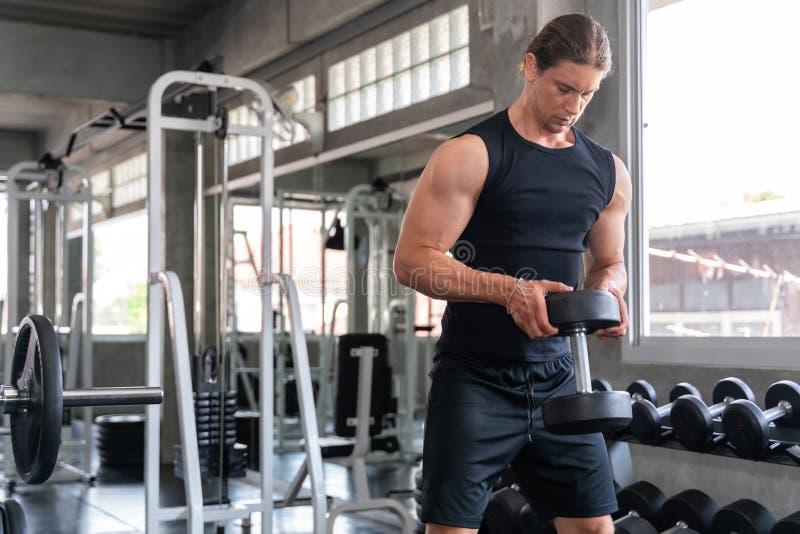 Un jeune homme très charmant faisant des exercices en gym photos stock