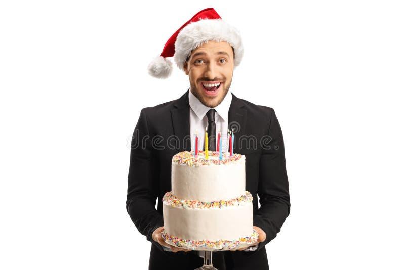 Un jeune homme très excité en costume portant un chapeau de Noël et tenant un gâteau photographie stock libre de droits