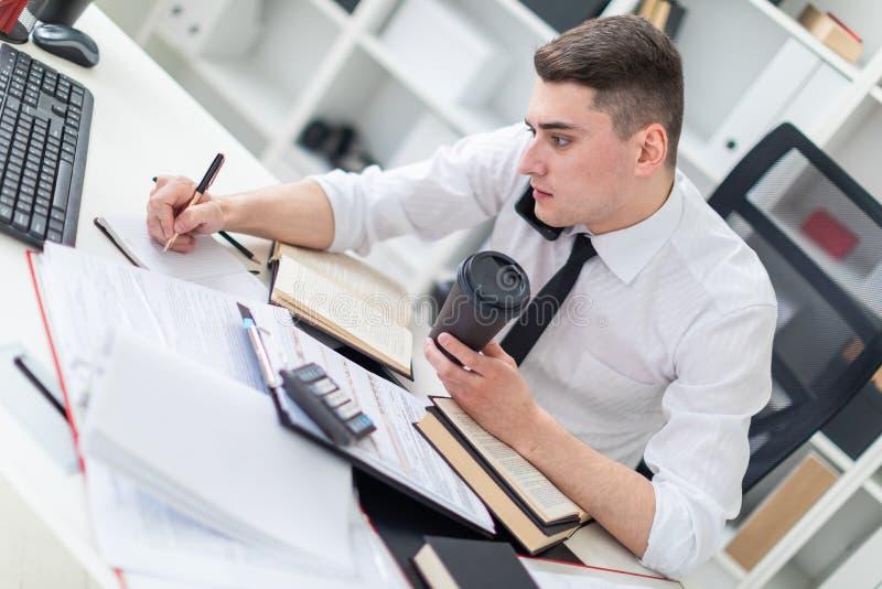 Un jeune homme travaillant à une table dans le bureau avec un livre, des documents et un ordinateur Il tient un verre de café photo stock
