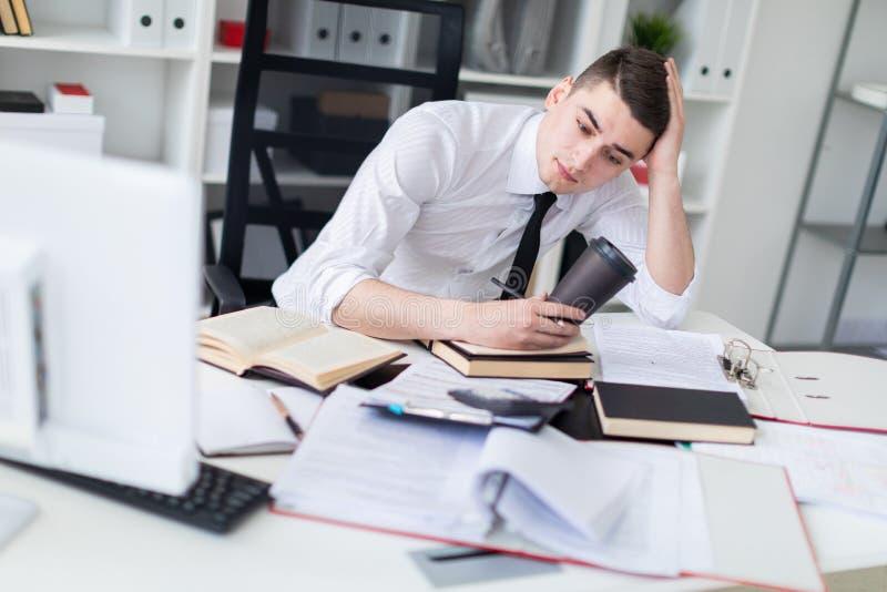 Un jeune homme travaillant à une table dans le bureau avec un livre, des documents et un ordinateur Il tient un verre de café images stock