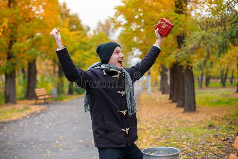 Un jeune homme a trouvé en parc un cadeau rouge photographie stock libre de droits