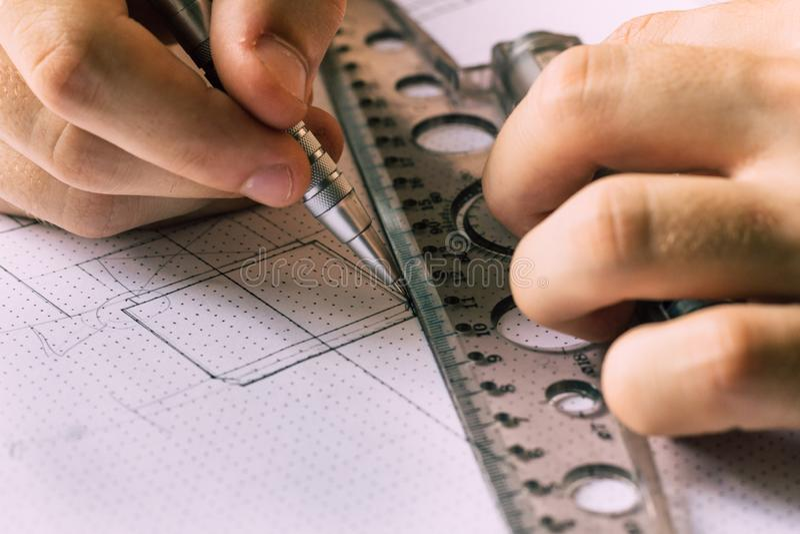 Un jeune ingénieur apprend à travailler avec des dessins photos libres de droits