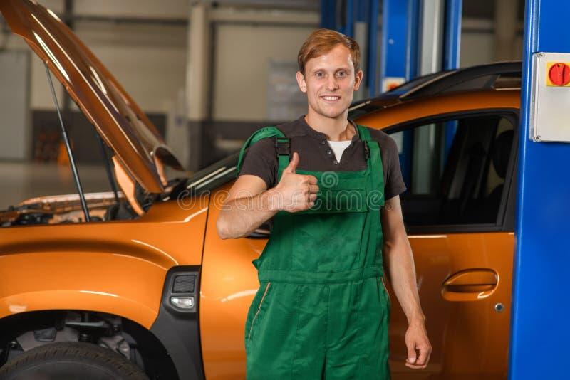 Un jeune mécanicien dans des combinaisons vertes montre devant un c orange images libres de droits