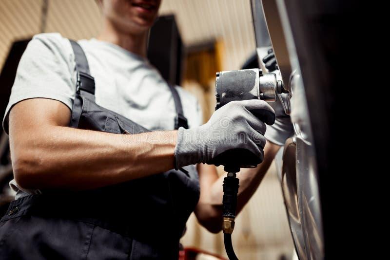 Un jeune mécanicien qualifié changeant un pneu d'une voiture soulevée Réparez l'atelier images stock