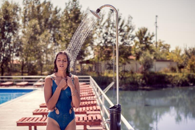 Un jeune modèle de femme adulte, position, l'eau versant la douche, e photos stock
