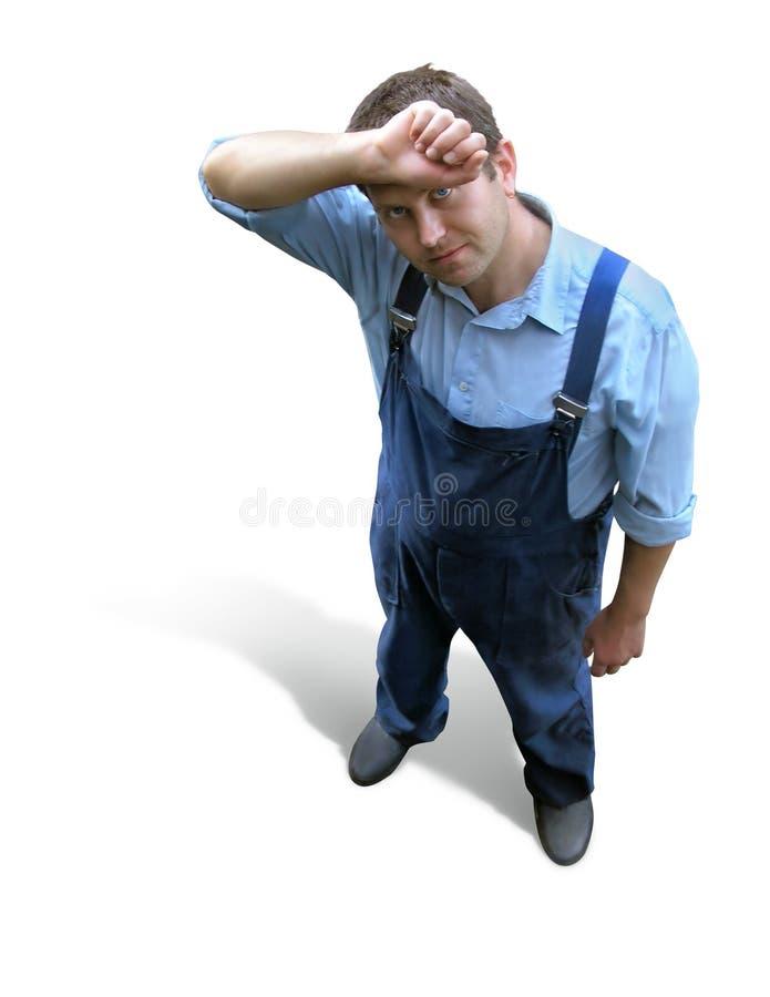 Un jeune ouvrier fatigué dans des vêtements de fonctionnement, regardés de ci-avant photos stock