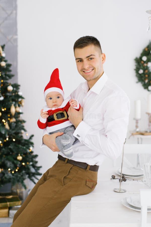 Un jeune père heureux vêtu d'une chemise blanche tient son fils en bas dans un petit costume de Père Noël et sourit Ils fêtent No image stock
