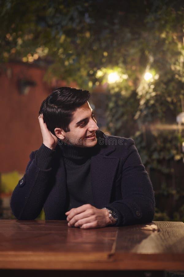 Un jeune portrait beau d'homme, se reposant dans le jardin de café à la table, nuit en longueur, souriant Tir de corps supérieur photo stock