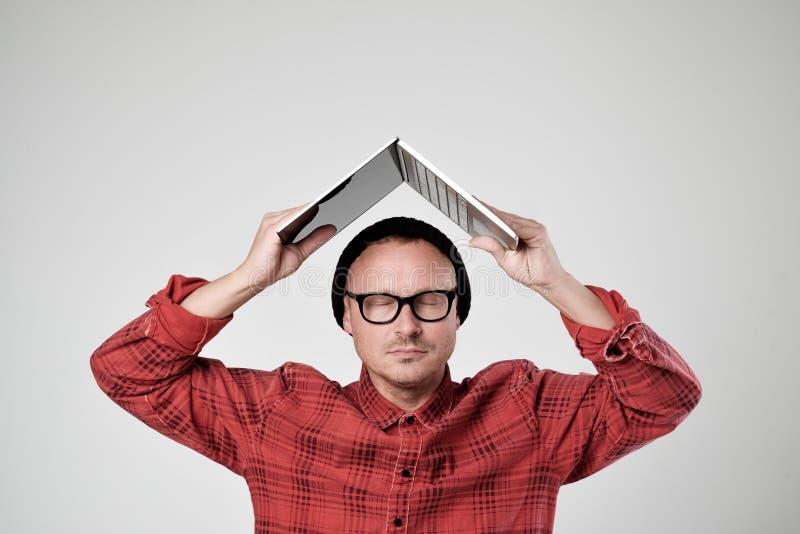 Un jeune programmeur dans un chapeau noir tient un ordinateur portable dans son Han image stock