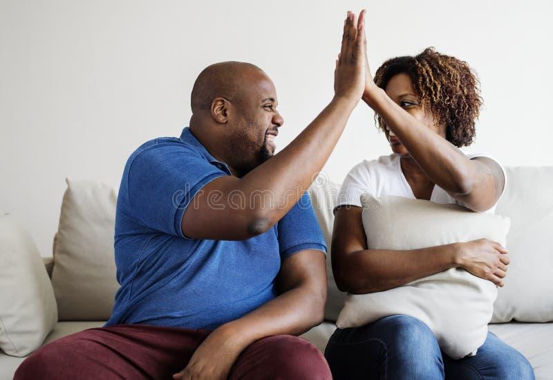 Un jeune succès africain de couples s'occupant ensemble haut cinq images stock