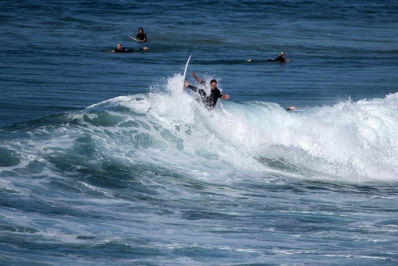 Un jeune surfer rentre la crête d'une vague images stock
