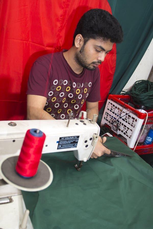 Un jeune tailleur Md Rashed Alam, vieillissent 28 drapeaux nationaux bangladais de fabrication chez Dhaka, Bangladesh photo stock