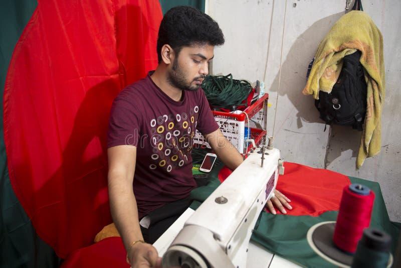 Un jeune tailleur Md Rashed Alam, vieillissent 28 drapeaux nationaux bangladais de fabrication chez Dhaka, Bangladesh photographie stock libre de droits