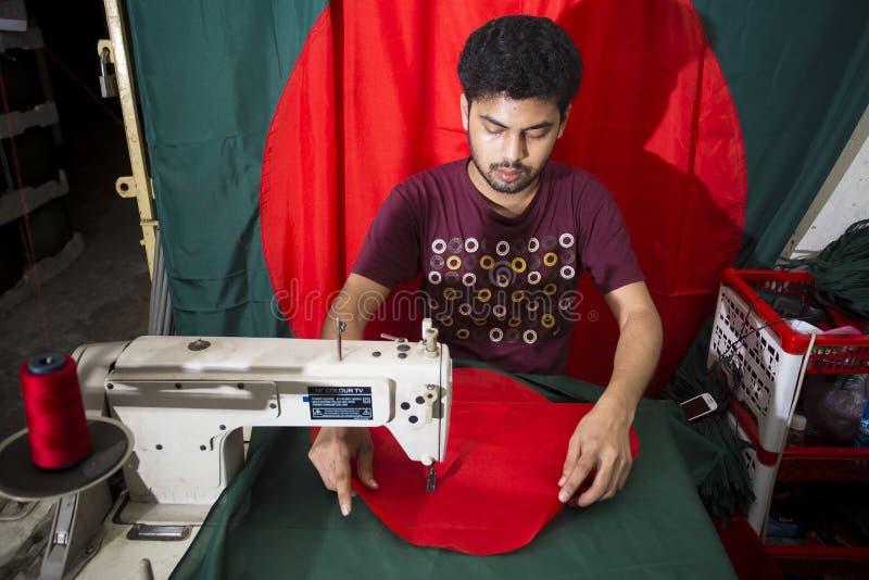 Un jeune tailleur Md Rashed Alam, vieillissent 28 drapeaux nationaux bangladais de fabrication chez Dhaka, Bangladesh photos stock