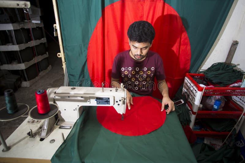 Un jeune tailleur Md Rashed Alam, vieillissent 28 drapeaux nationaux bangladais de fabrication chez Dhaka, Bangladesh photo libre de droits