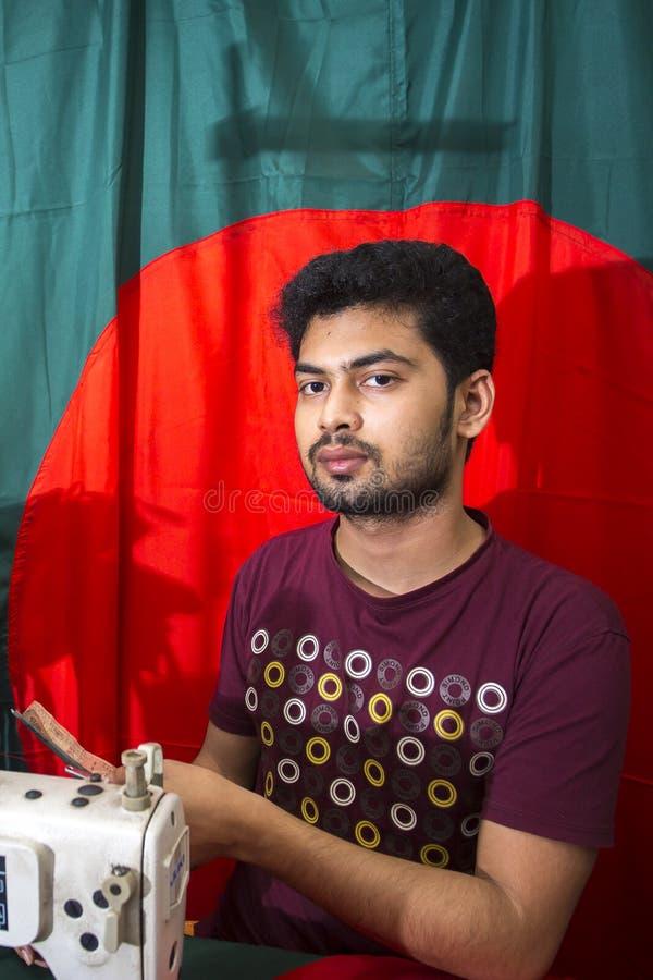 Un jeune tailleur Md Rashed Alam, vieillissent 28 drapeaux nationaux bangladais de fabrication chez Dhaka, Bangladesh images libres de droits