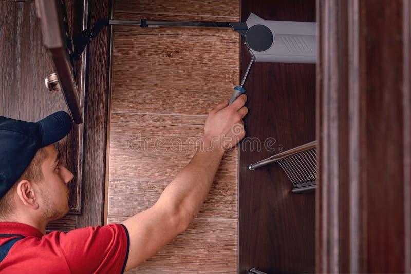 Un jeune travailleur assemble les meubles en bois modernes de cuisine photo stock