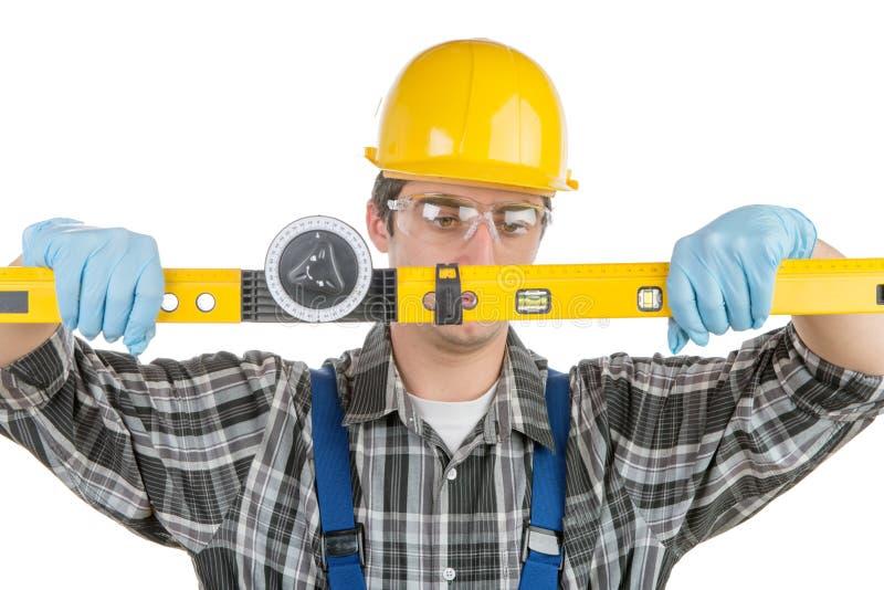 Un jeune travailleur avec un niveau photos libres de droits
