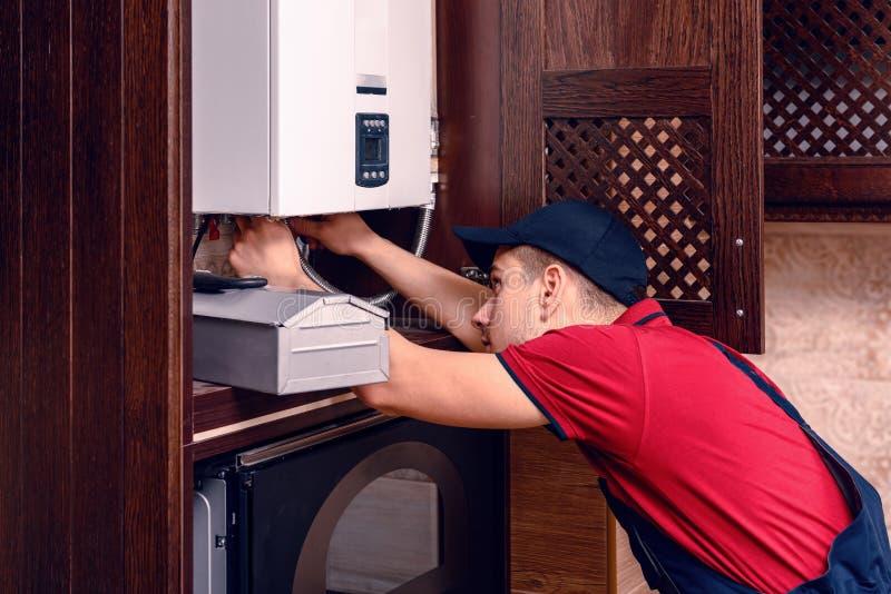 Un jeune travailleur qualifié règle la chaudière de gaz avant emploi photos stock