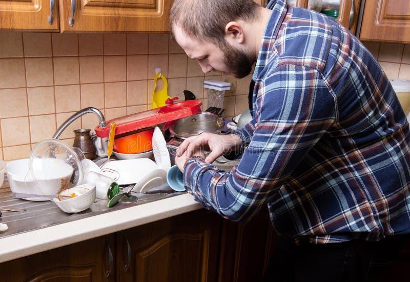 Un jeune type barbu regarde sa montre et est choqué par la quantité de plats sales se situant dans l'évier de cuisine Il n'a pas image libre de droits