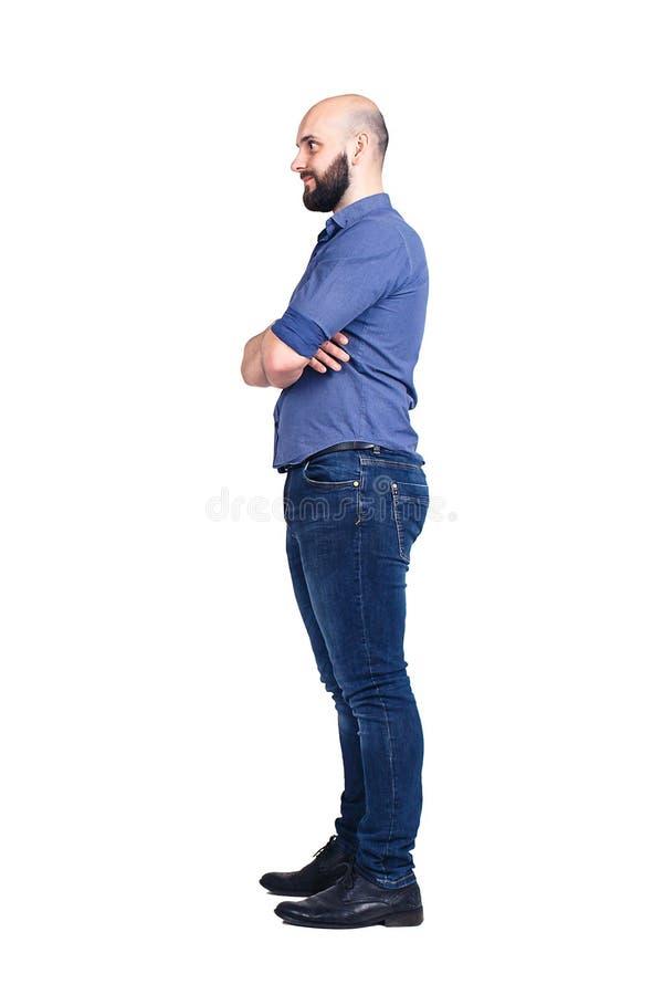 Un jeune type barbu se tient en longueur et regarde loin D'isolement sur le blanc photographie stock libre de droits